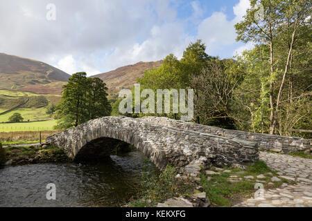 Lake District, Cumbria - a packhorse bridge over the River Derwent near Rosthwaite, in Borrowdale - Stock Photo
