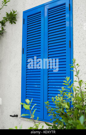 window with blue shutters - Stock Photo