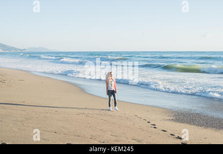 Young blond woman in red checkered shirt, jeans and white sneakers walking along beach and the stormy ocean on sunny - Stock Photo