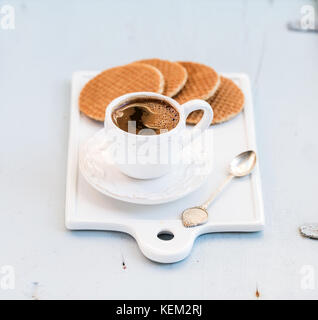 Dutch caramel stroopwafels and cup of black coffee on white ceramic serving board over light blue wooden backdrop, - Stock Photo