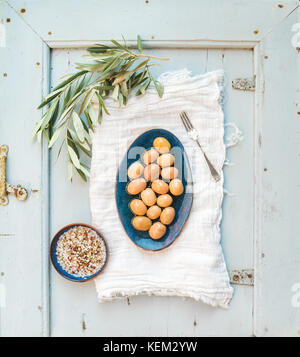 Green big olives in blue ceramic plate with tree branch and spices on kitchen towel over light blue background, - Stock Photo