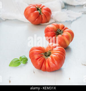Fresh ripe hairloom tomatoes and basil leaves over light blue wooden background - Stock Photo