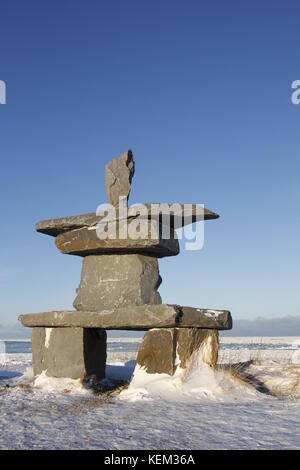 Inukshuk (Inuksuk) found near Churchill, Manitoba with snow on the ground in early November, Canada - Stock Photo