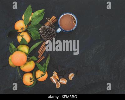 Christmas or New Year frame. Fresh mandarines with leaves, cinnamon sticks, vanilla, pine cone and mug of hot chocolate - Stock Photo