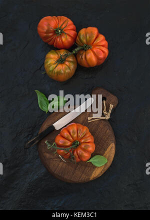 Fresh ripe hairloom tomatoes and basil leaves on rustic wooden board over black stone background., top view - Stock Photo