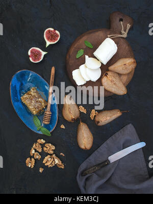 Appetizer set. Roasted pears, goat cheese on rustic dark wooden board, fig, honey and walnuts over black stone background, - Stock Photo