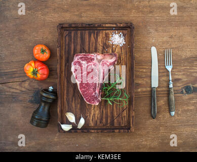 Raw fresh meat t-bone steak with garlic cloves, tomatoes, rosemary and salt on serving board over rustic wooden - Stock Photo