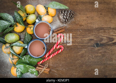 Christmas or New Year frame. Fresh mandarins with leaves, cinnamon sticks, pine cone, hot chocolate in mugs and - Stock Photo