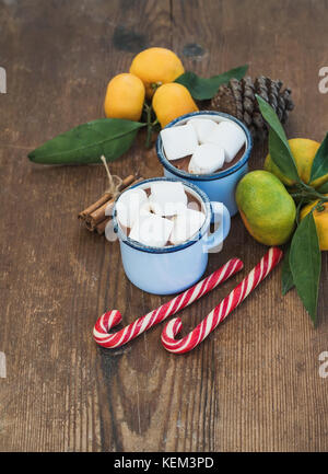 Hot chocolate in enamel metal mugs, fresh mandarines, cinnamon sticks, pine cone and candy canes over rustic wooden - Stock Photo