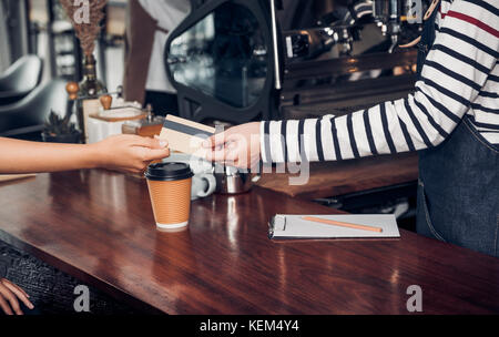 customer pay coffee drink with credit card to barista,Close up hand paid for to go coffee cup at counter bar in cafe,Food and drink business,billing p