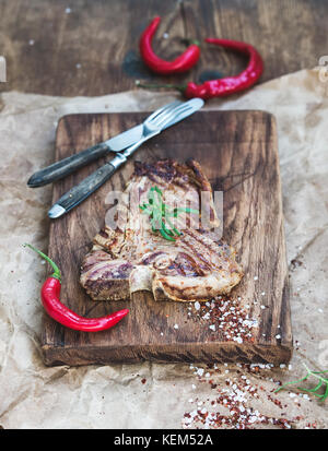 Cooked meat t-bone steak on serving board with red chili peppers, spices and fresh rosemary over oily craft paper, - Stock Photo