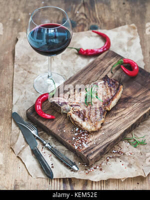 Cooked meat t-bone steak on serving board with roasted tomatoes - Stock Photo