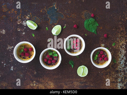 Creme brulees with raspberries and mint in white bowls over grunge metal backdrop. Top view - Stock Photo