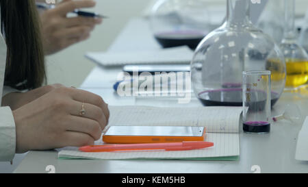 Students at work in the laboratory of chemistry take notes in a notebook. Female Pupil Using phone In Science Lesson. - Stock Photo
