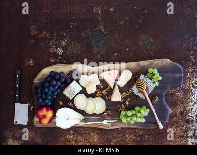 Wine appetizers set: French cheese selection, honeycomb, grapes, peach and walnuts on rustic wooden board over dark - Stock Photo