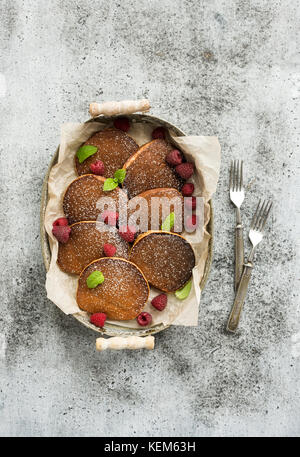Breakfast set. Homemade buckwheat pancakes with fresh raspberry in  serving tray, kitchen napkin, vintage silverware - Stock Photo