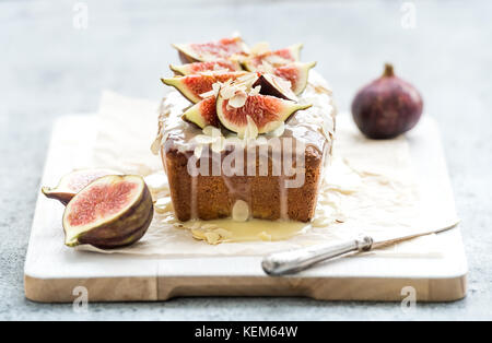 Loaf cake with figs, almond and white chocolate on wooden serving board over grunge background, selective focus. - Stock Photo