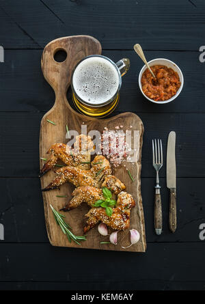 Fried chicken wings on rustic serving board, spicy tomato sauce, herbs and mug of light beer over black wooden backdrop - Stock Photo