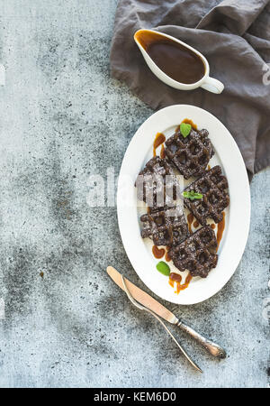 Chocolate Belgian waffles with salted caramel sauce and mint on white ceramic serving plate over grunge background, - Stock Photo