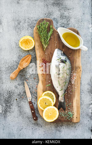 Fresh uncooked dorado or sea bream fish with lemon, herbs, oil and spices on rustic wooden board over grunge backdrop - Stock Photo