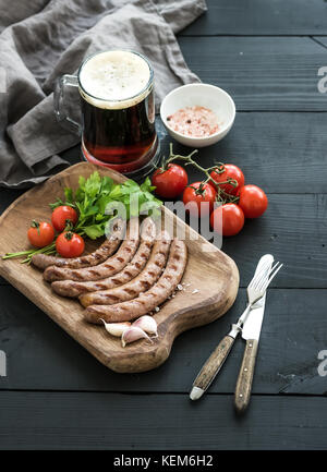Grilled sausages with vegetables on rustic serving board and mug of light beer over black wooden backdrop. - Stock Photo