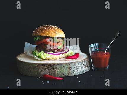 Fresh homemade burger on wooden serving board with spicy tomato sauce, sea salt and herbs over black  background. - Stock Photo
