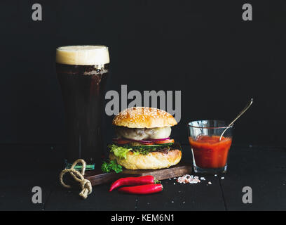 Fresh homemade burger on wooden serving board with spicy tomato sauce, sea salt, herbs and glass of dark beer over - Stock Photo