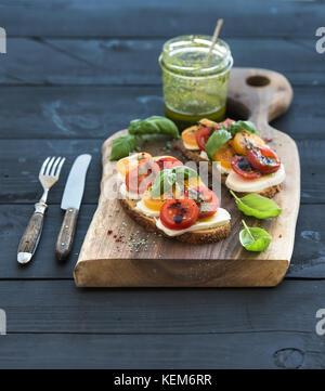 Tomato, mozzarella and basil sandwiches on dark wooden chopping board, pesto jar, dinnerware over black background - Stock Photo