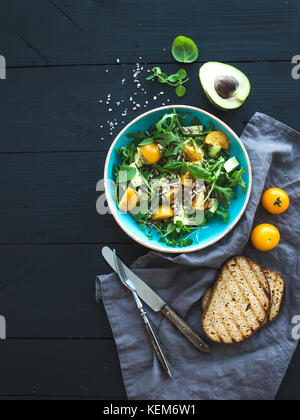 Bowl of green salad with avocado, arugula, cherry tomatoes and sunflower seeds, grilled bred slices, fresh herbs - Stock Photo