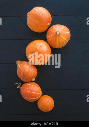 Ripe pumpkins over black rustic wooden backdrop, top view - Stock Photo