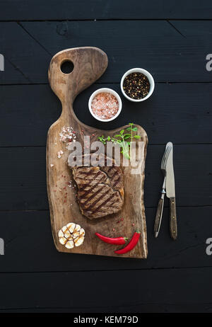 Grilled ribeye beef steak with herbs and spices on walnut cutting board over black wooden background - Stock Photo