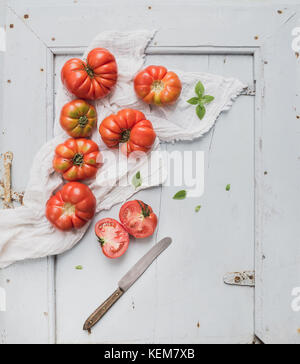 Fresh ripe hairloom tomatoes and basil on rustuc blue wooden surface - Stock Photo
