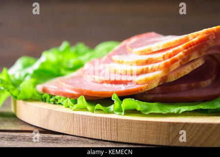 Sliced ham with fresh green lettuce leaves on a round cutting board. Meat products on a brown wooden table. - Stock Photo