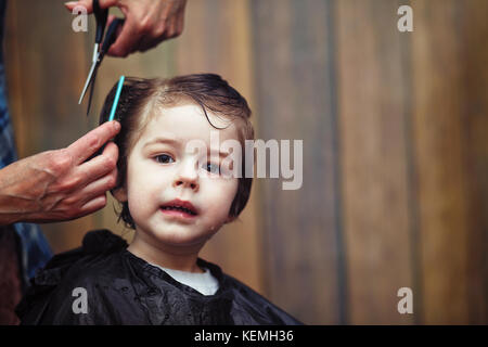 A little boy is trimmed in the hairdresser's  - Stock Photo