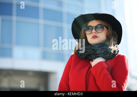 Cute businesswoman in a red coat against a background of glass - Stock Photo