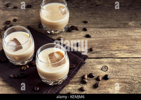Irish cream coffee liqueur with ice, chocolate candies and coffee beans over rustic wooden background - homemade festive alcohol drink