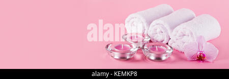 Towels, candles and orchid flowers for a spa relaxation on a pink background - Stock Photo