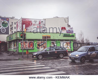 Cars waiting in front of a zebra crossing and red traffic lights next to a small Krecik grocery shop in the city - Stock Photo