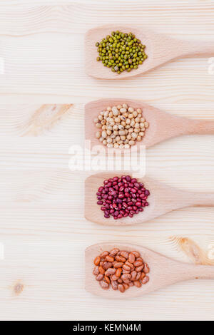 Assortment of beans and lentils in wooden spoon on wooden background.  soybean, mung bean , red bean and brown pinto - Stock Photo