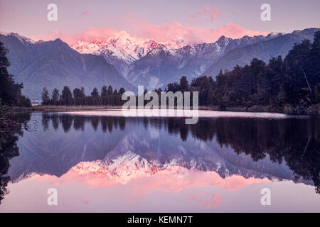 Lake Matheson at sunset with snow covered Mount Tasman and, in the cloud, Aoraki-Mount Cook, New Zealand's highest - Stock Photo