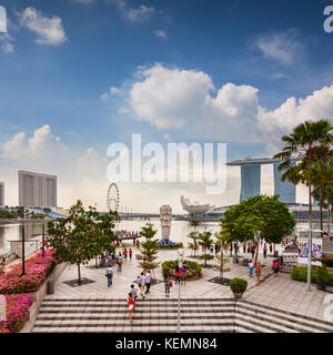 Tourists near the Merlion and looking out over some of the major tourist attractions of Singapore - the Marina Bay - Stock Photo