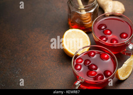 cranberries lemon ginger drink in a glass cup, honey, half a lemon, slices of ginger on a dark background - Stock Photo