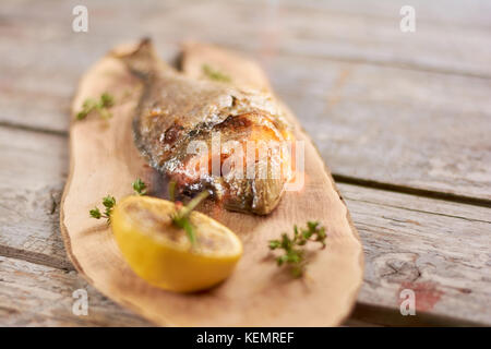 Grilled dorado fish with lemon. Roasted dorado fish with a piece of lemon on wooden table at restaurant. - Stock Photo