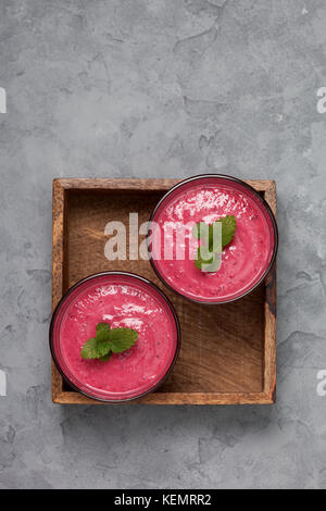 red berry fruit smoothies in glasses on a gray concrete background. view from above. copy space - Stock Photo