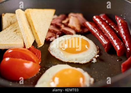 Full english breakfast in pan. English breakfast in pan with fried eggs, sausages, bacon, tomatoes and toasts. Traditional - Stock Photo