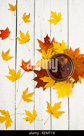 Thanksgiving background: Pumpkins and fallen leaves on white wooden background.  Halloween or Thanksgiving day or - Stock Photo