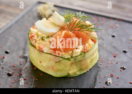 Olivier salad with salmon and tobiko caviar. Tasty olivier salad served with salmon, tobiko caviar, dill and eggs. - Stock Photo