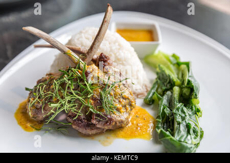 Grilled Lamb steak with spicy yellow sause and green vegetable on jasmine rice. - Stock Photo