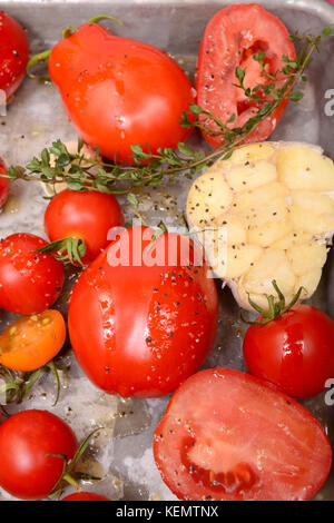 Freshly roasted tomatoes, garlic, onions, and herbs in preparation for a delicious tomato soup - Stock Photo