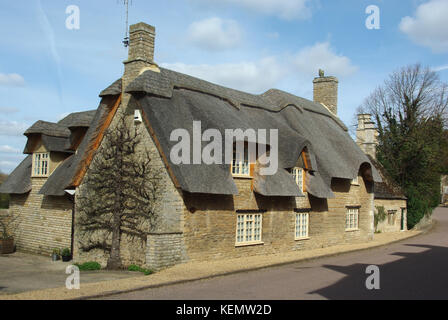 Detached house, with chimneys and a thatched roof, in the village of Duddington, Northamptonshire, UK - Stock Photo